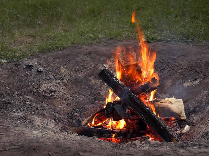 Small fire in backyard fire pit - travel - camping danger