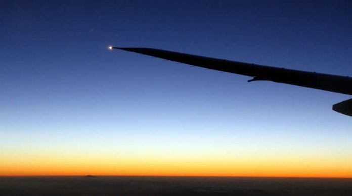 Travel photo - plane wing in the air - moon and mercury during sunset